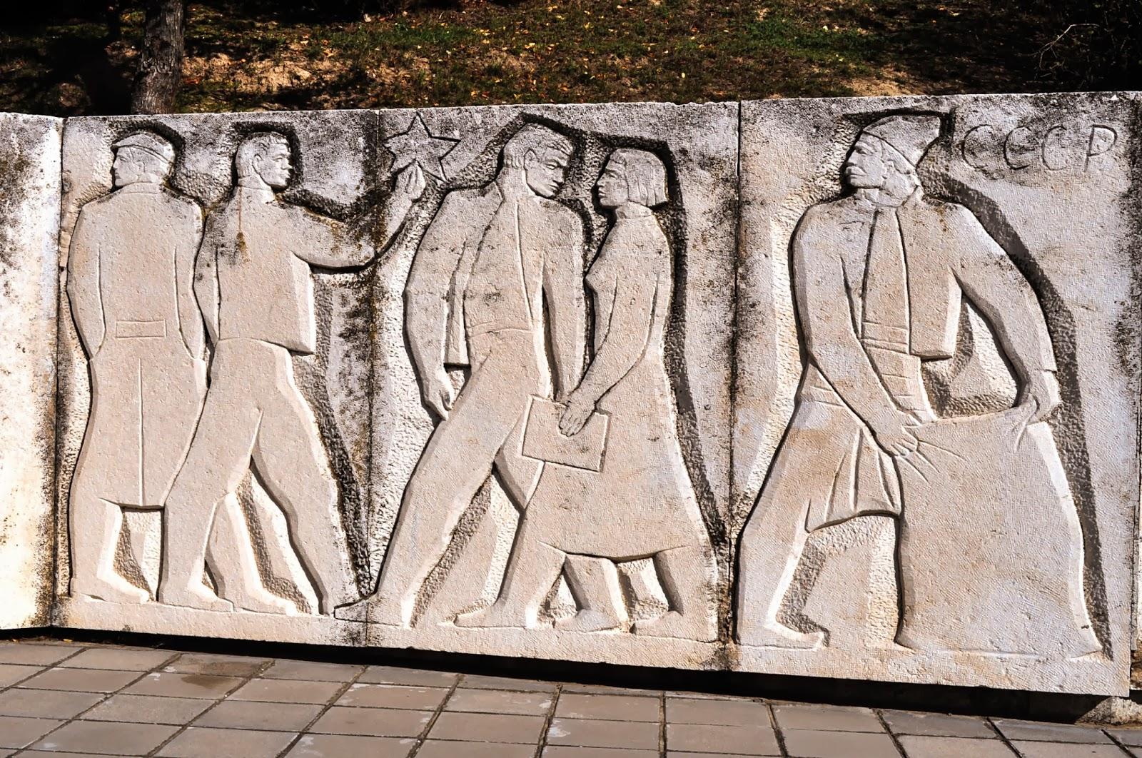 """В центъра на Оряхово попадаме на следното произведение на изкуството от времето на социализма. Сякаш дете с несигурна ръчичка е пресъздало представите си за """"човека на новото време"""": селянина, работника и младите представители на художествено-творческата интелигенция."""