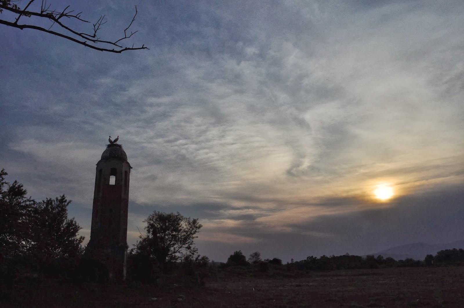 """Нощта бавно се спуска над църквата """"Св. Атанасий"""" край язовира под зоркия поглед на семейство щъркели."""