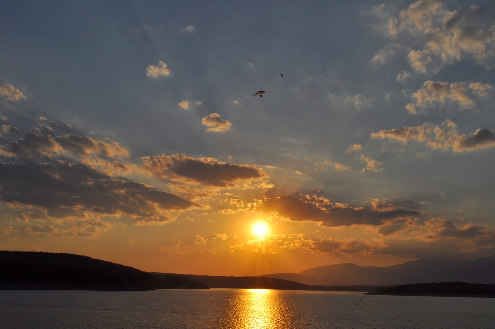 Слънцето с охота се сбогува с копринената водна повърхност, а онази точка в небето е моторен делтаплан. Каква ли ще да е гледката отгоре?