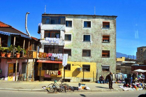Навлизаме в предградията на Тирана. Прилича ми на Тунис или на Турция, а може би на Факултето?