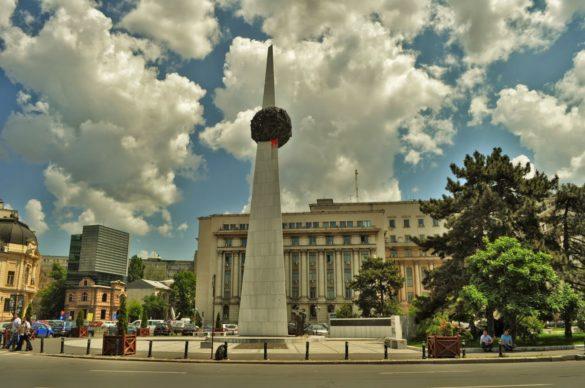 """Площадът на революцията с паметника на Прераждането, издигнат в чест  на румънските борци срещу режима на Чаушеску. Тук се е намирал централният щаб на Румънската компартия, където Чаушеску и неговата Елена се спотайвали, притаили дъх от ужас и недоумение, докато навън многохилядни гърла ревели """"Изчадия"""", """"Зверове"""" и """"Смърт"""". В даден момент демонстрантите нахлули в комунистическото леговище в опит да линчуват височайшето семейството, но то пък се изнизало с хеликоптер от покрива на сградата.  Така или иначе разстрелът не му се разминал."""