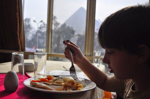 Калин безропотно похапва блудкава на вкус риба на фона на пирамидите .